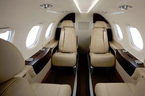 Kabine einer Embraer Phenom 100 mit beigen Ledersitzen